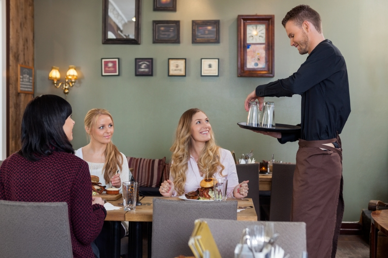 5156890-waiter-with-tray-of-glasses-while-female-customers-having-meal